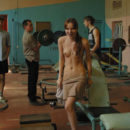 Nude redhead teen posing in an old gym
