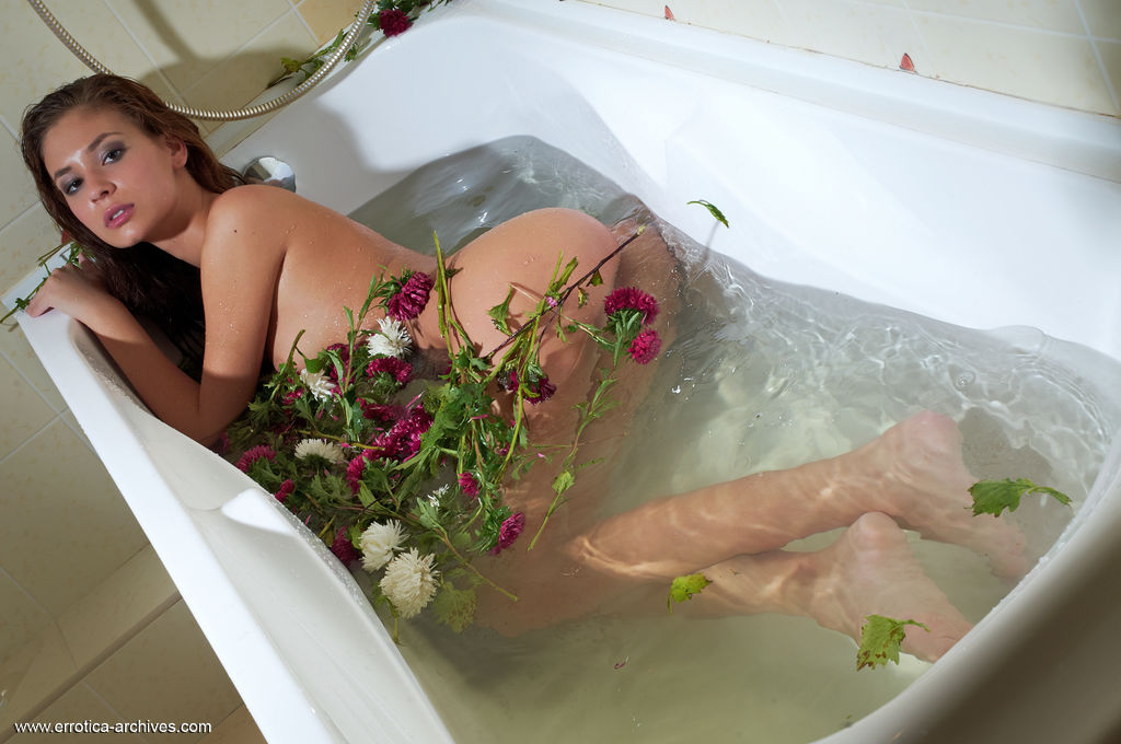 On a bath filled with water and delicate flowers, Afrodita portrays a playful, stunning nymph with a seductive gaze.