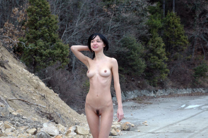 Skinny brunette at blockage in the mountain road