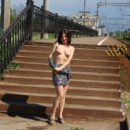 Smiling girl Vika walks on railroad station