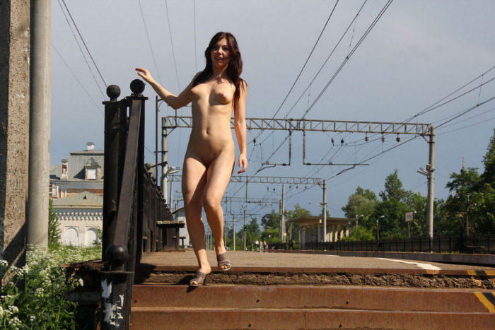 Smiling girl Vika walks on railroad station