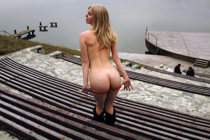 Teen blonde removes red panties by the river