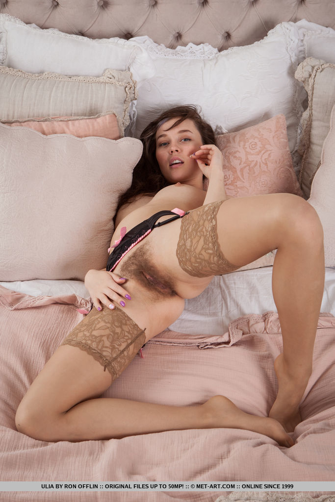 Ulia sensually poses on the bed as she displays her unshaven pussy.