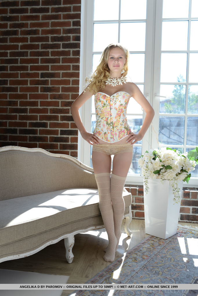 Wearing a knee-high off-white stockings, floral corset, and matching lace panty that adds a touch of elegance, Angelika D poses enticingly with so much finesse.