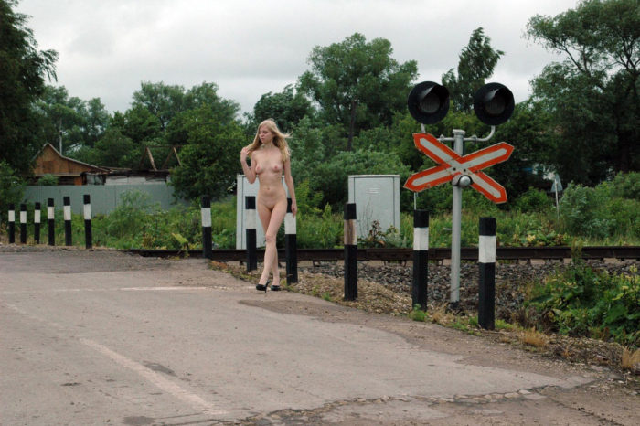 Young blonde with skinny body at railroad