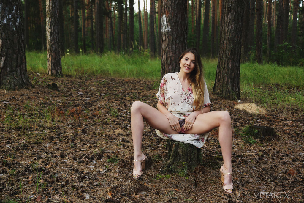 Kira takes off her top and panties and starts masturbating in the middle of the woods