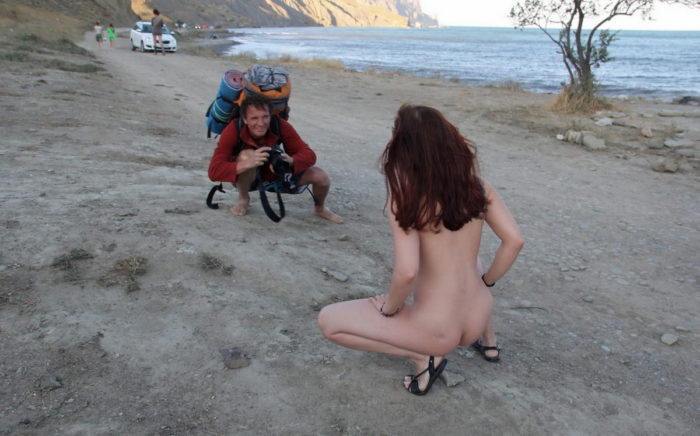 Pierced redhead teen posing in front of a photographer on the beach