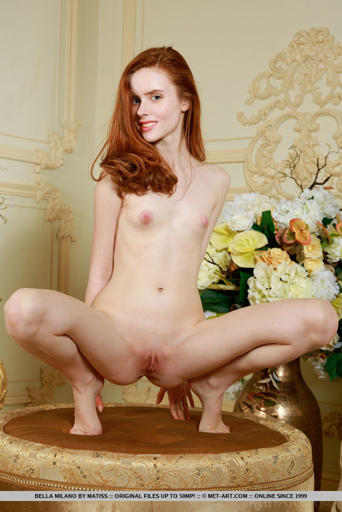 Redhead Bella Milano displays her petite body by the mirror.