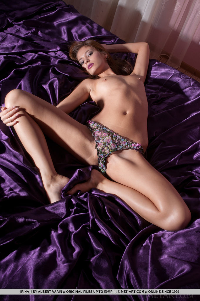 The stunning Irina J sprawled invitingly on top of silky purple sheets, with teasing looks and tempting poses.