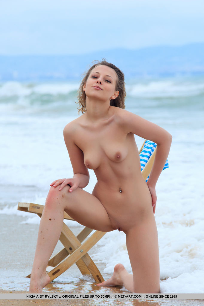 Top model Nikia A having fun by the beach. She strips her blue top with black bikini and flaunts   her amazing physique and small puffy breasts on the chair.