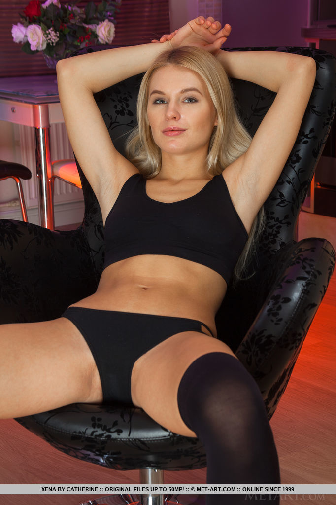 Wearing a sheer black thigh-high stockings, black cropped top, and matching black panty, Xena emphasizes her gorgeous, well-toned legs with erotic and provocative postures.