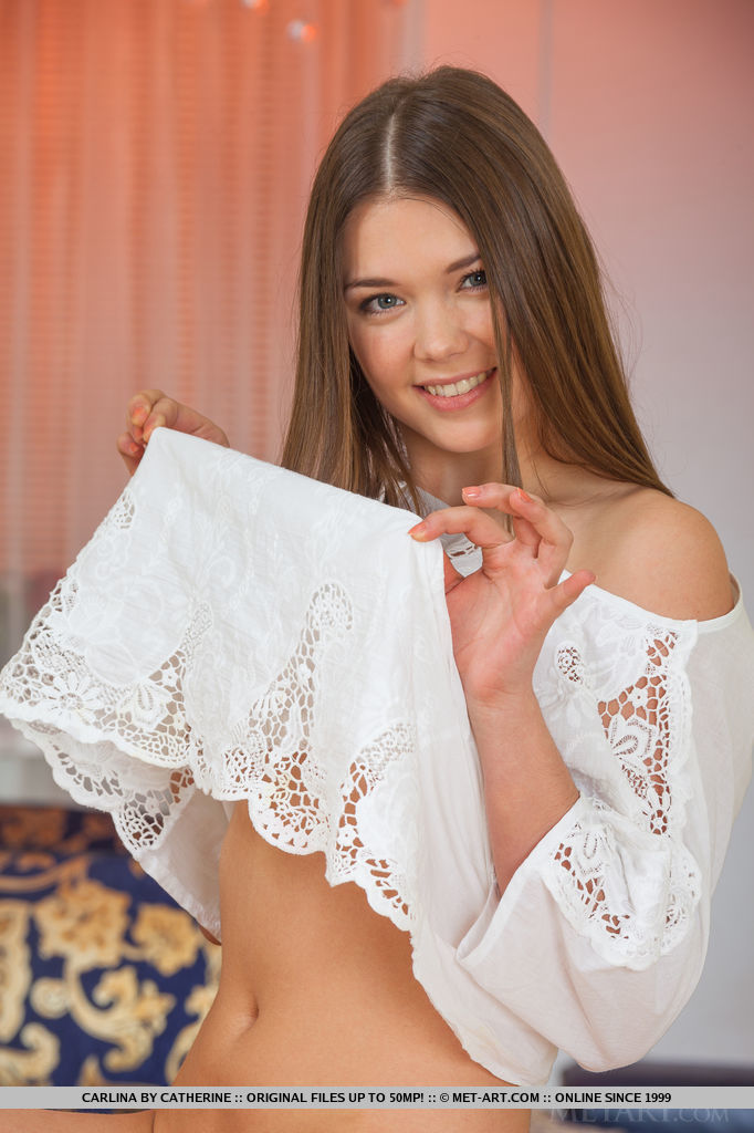 Adorable newcomer Carlina, strips her white dress and showcases her nubile body and   delectable snatch on the couch.