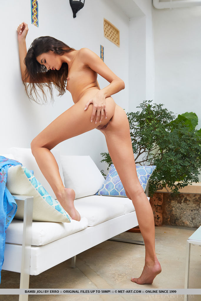 Bambi Joli displays her petite body and sweet ass on the couch.