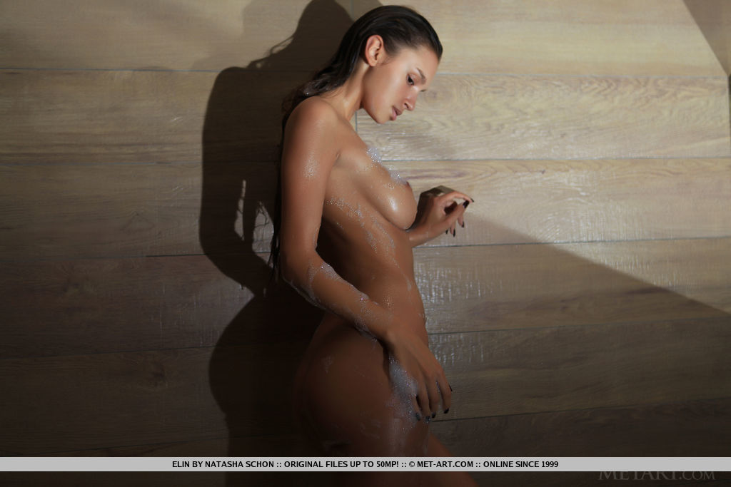 Elin's tight and curvy body covered in white, frothy soap suds