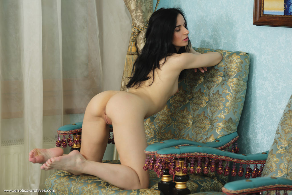Irida bares her naked body with erect nipples and small pussy on the chair.