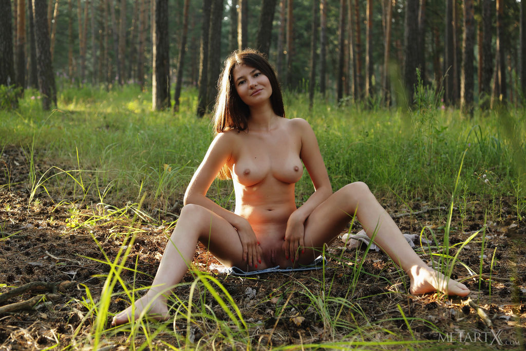 Melisia gets naked in the woods and shows off her breasts and shaved snatch
