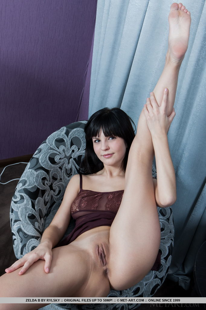 The smiling, exuberant Zelda B, happily posing and teasing from the couch to the bed, evoking a naturally delightful presence as she exhibits her fresh, young body with rosy, pink nipples and smooth legs.