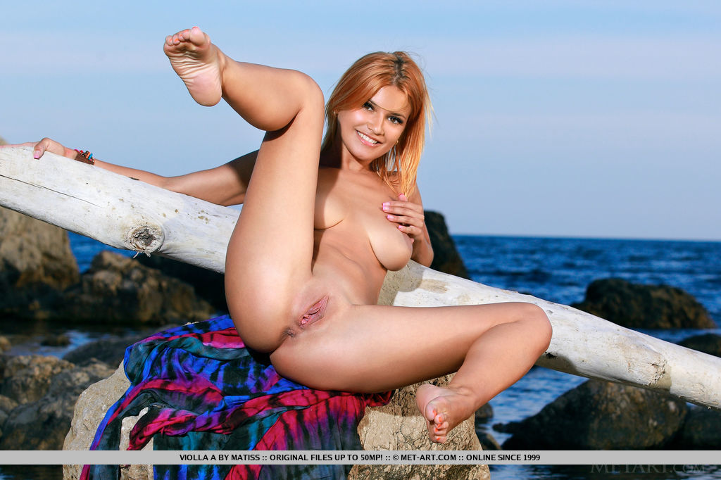 Violla A bright, cheerful smile and enthusiastic posing make a breathtaking view on the rocky seaside terrain.