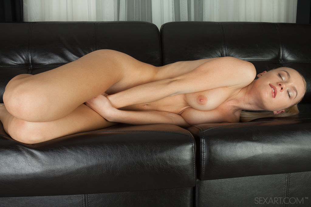 Xena looks hot and ready for some masturbation fun.  She is naked sitting on her black leather couch fondling her nipples.  It doesn't take long for her to get aroused and plunge her finger into her hot, wet hole.
