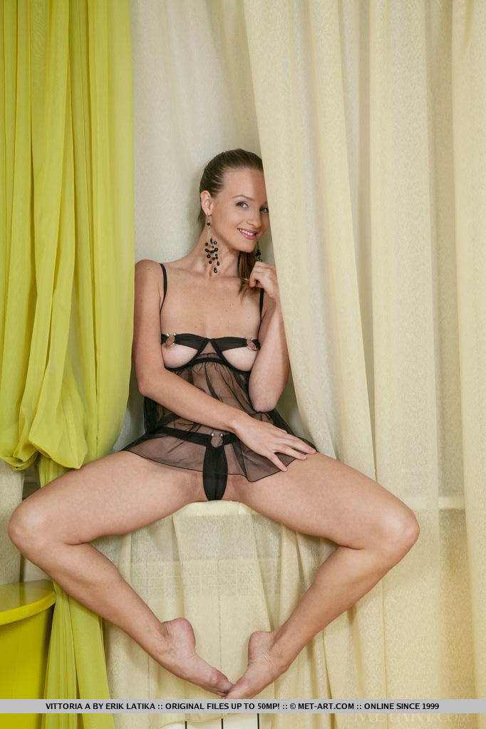 A playful Victoria proudly posing in her sheer black lingerie dress, showcasing her well-toned body.