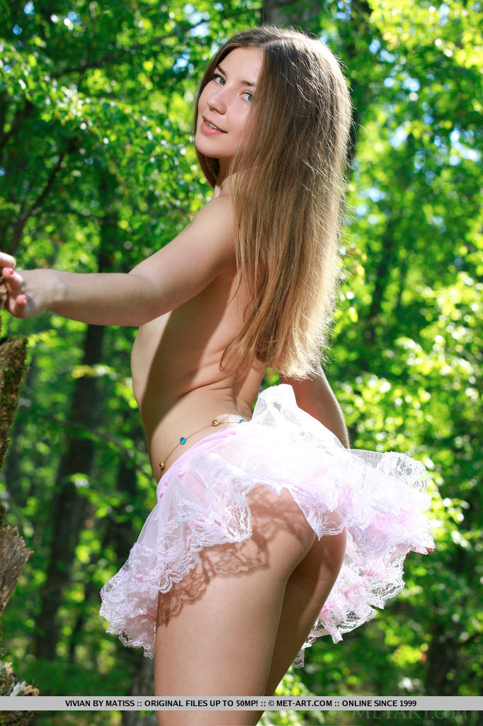 A sheer pink frilly skirt adorns Vivian's smooth, cute rump, complimenting slim legs and shaved pussy as she poses under a tree.