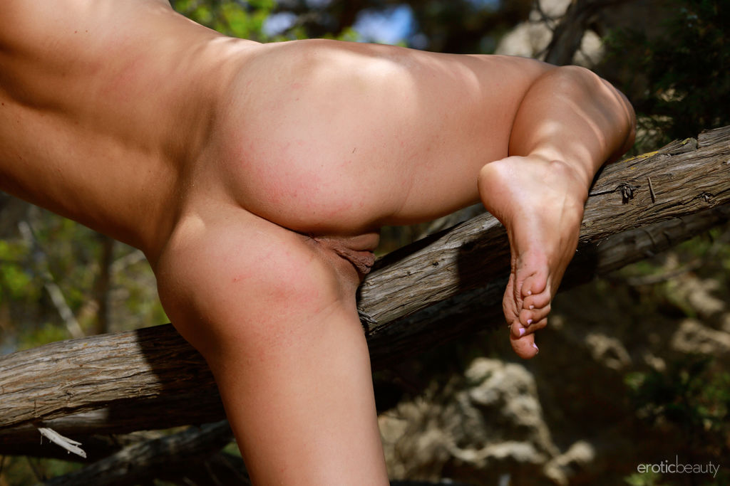 Emmy playfully poses outdoors as she flaunts her sexy body by the tree.
