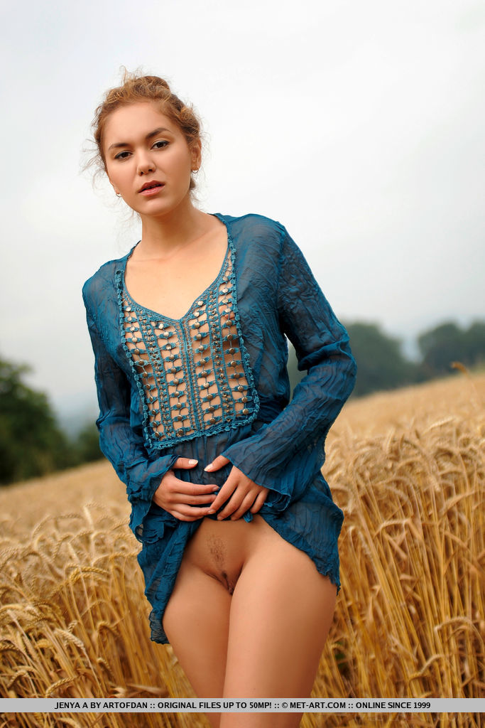 Jenya A strips in the field as she bares her slender body and meaty pussy.