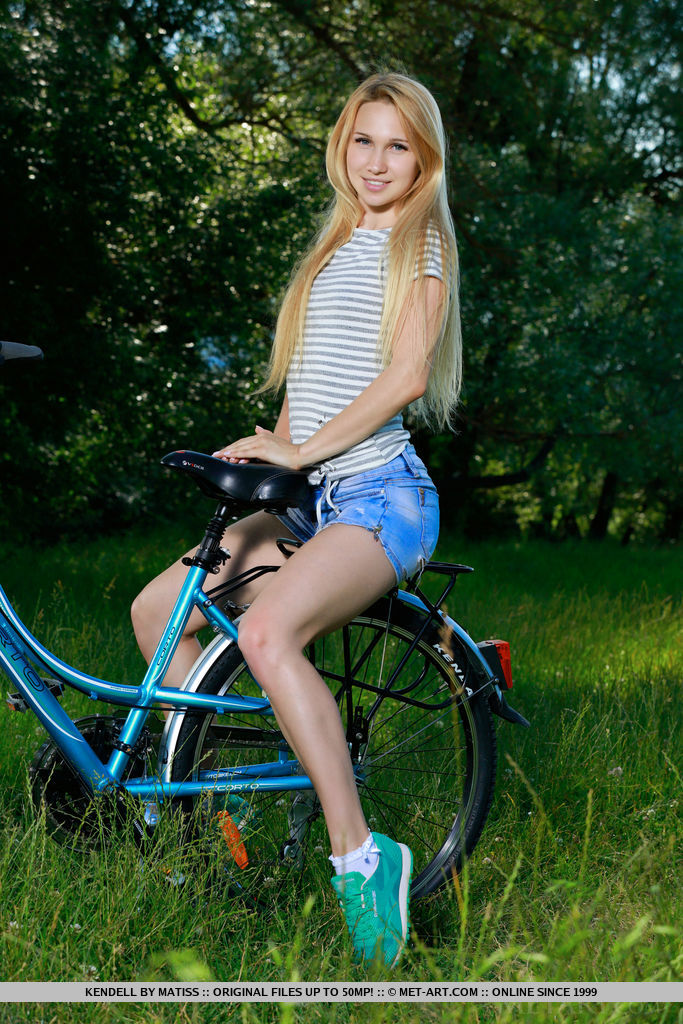 Kendell rides her bike outdoors as she bares her slender body and small pussy.