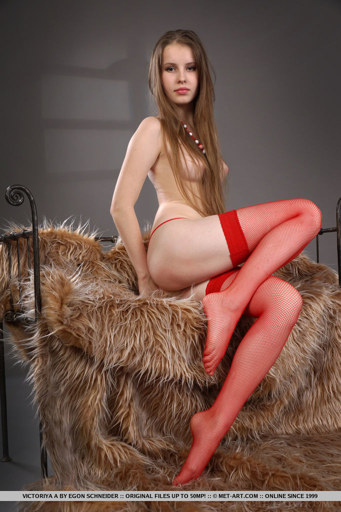 Victoriya A performs a sensual tease as she unrolls her red stockings before spreading her legs wide open on top of a luxurious fur rug.