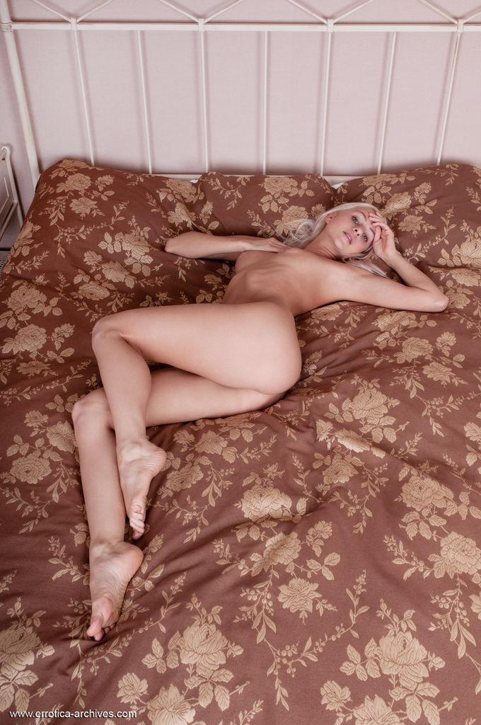Viviene poses on the bed as she bares her puffy tits and trimmed pussy.