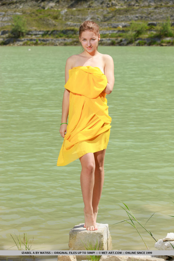 A bright yellow cloth hugs Izabel A's naked body as she poses enthusiastically by the river.