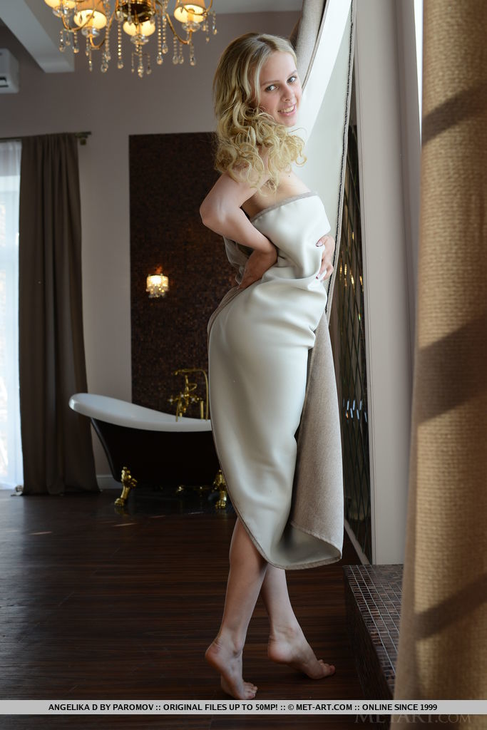 Angelika D playfully poses with a window curtain, the silky material hugging her smooth, slender body.