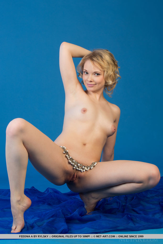 Blue-eyed Feeona A looks delicate and sweet against the blue background, posing in white lace panty.