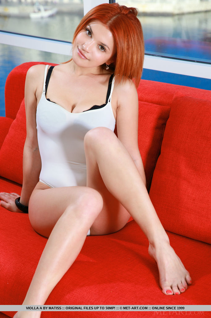 Sizzling redhead Violla A wearing a white one-piece bikini that showcases her tight yet curvy body.