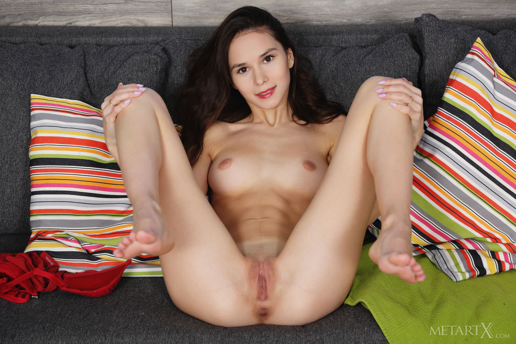 Leona Mia shows off her slim, nubile body before masturbating in the sofa