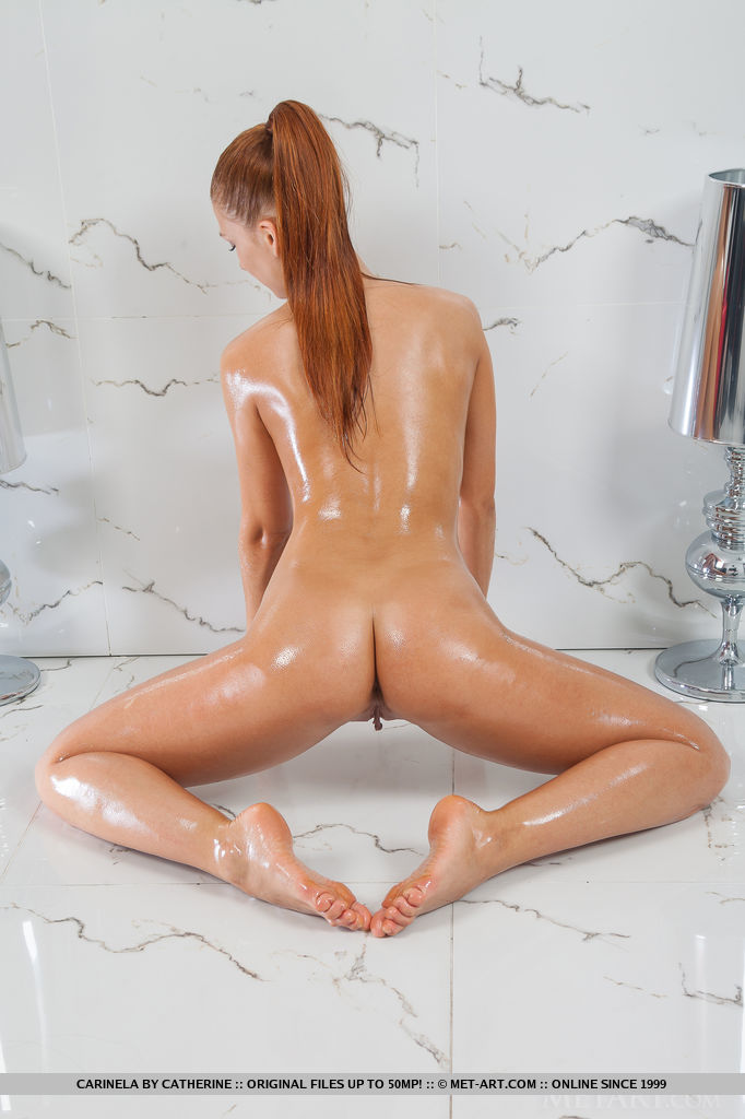 A stunning view of Carinela s oiled body as she poses sensually in front of the camera.