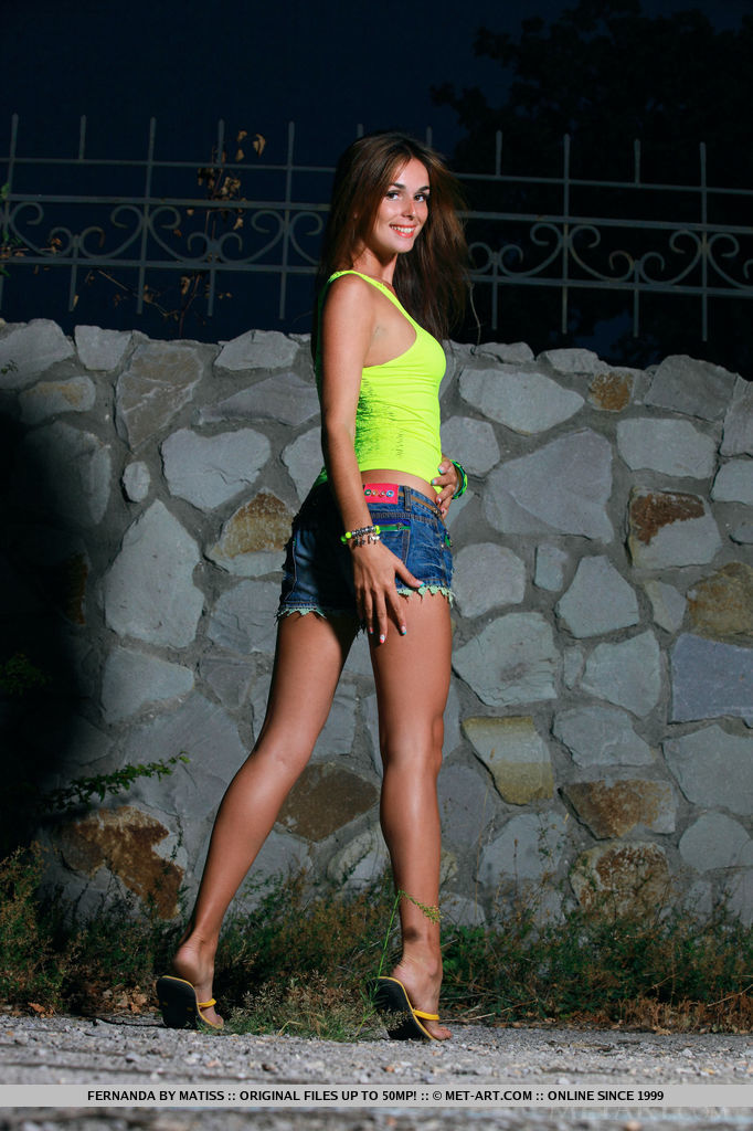 Fernanda looks fresh and vibrant at dusk, her stunning beauty and athletic physique complimented by her bright green tank top and cut-off denim shorts.