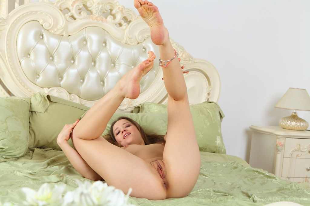 Taissia A has that sweet innocent girl next door look.  Well, that is until you find her in her bedroom laying sprawled out naked on her lovely celery green satin sheets playing with her gaping pussy.