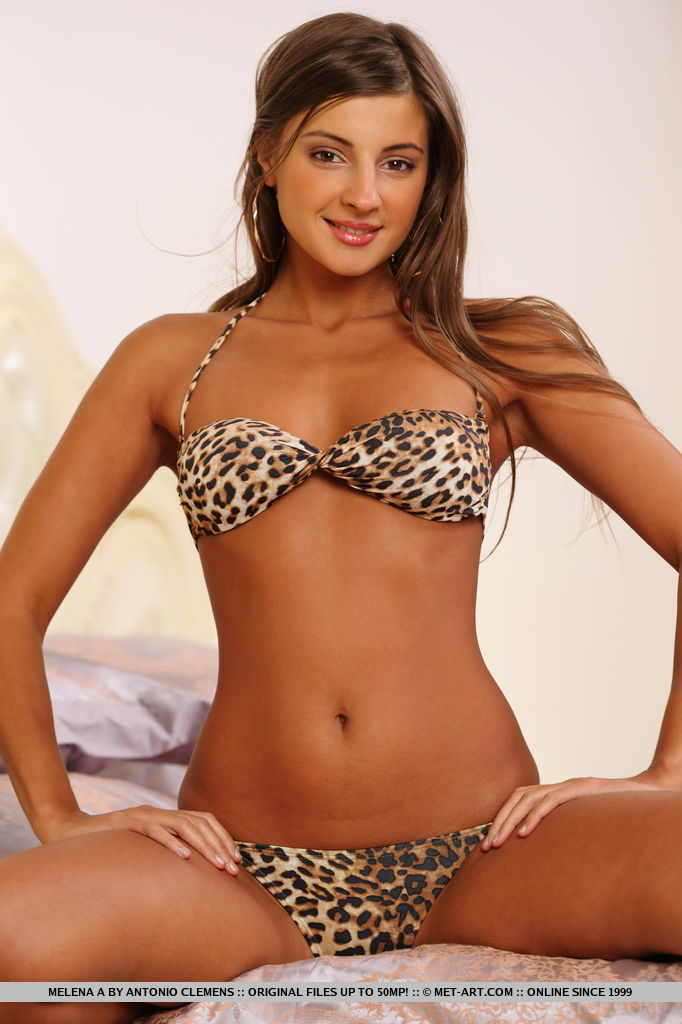 With her effortless allure and elegant charm, Melena A performs a slow, erotic striptease on the bed.