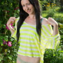 Fun-loving babe Janelle B naughtily posing in the garden, showing off her smooth, fair body with puffy assets.