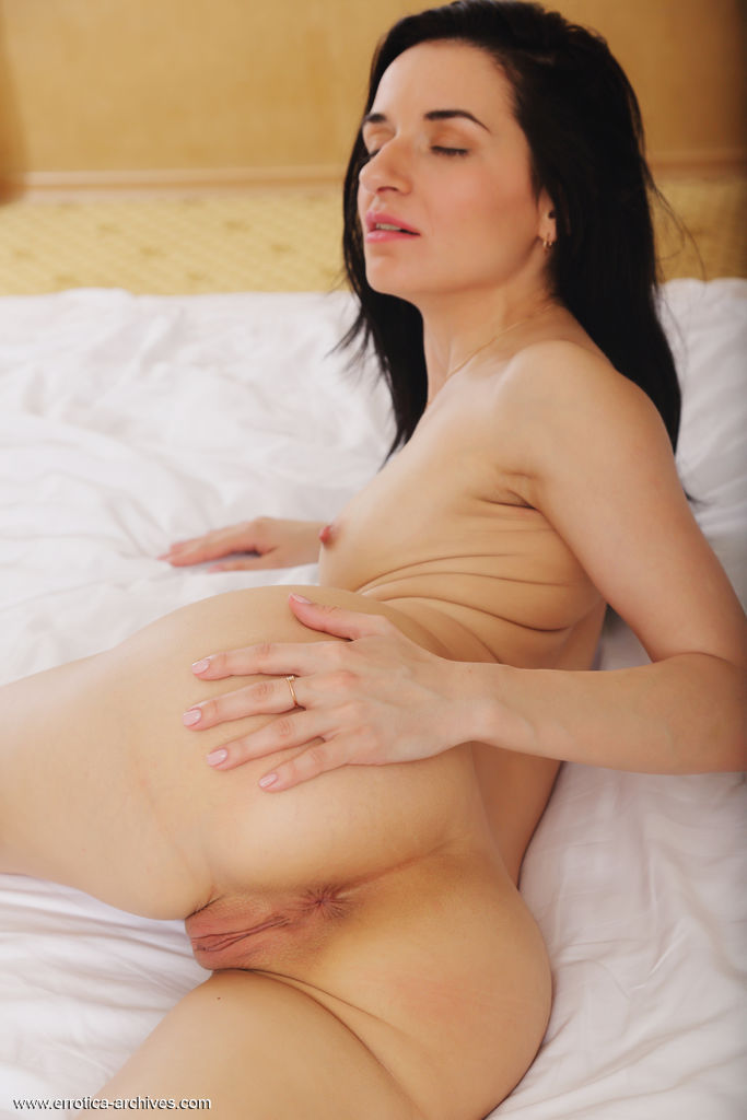 Irida spreads her legs wide open baring her delectable pussy on the bed.
