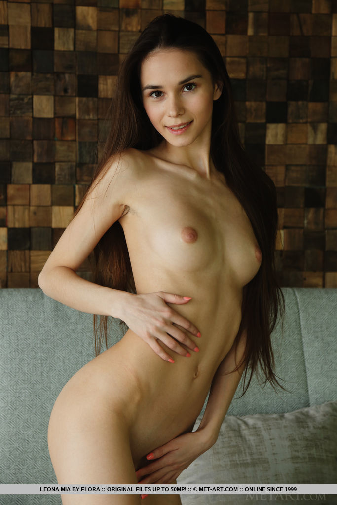 Leona Mia strips on the couch baring her petite body and sweet cherry.