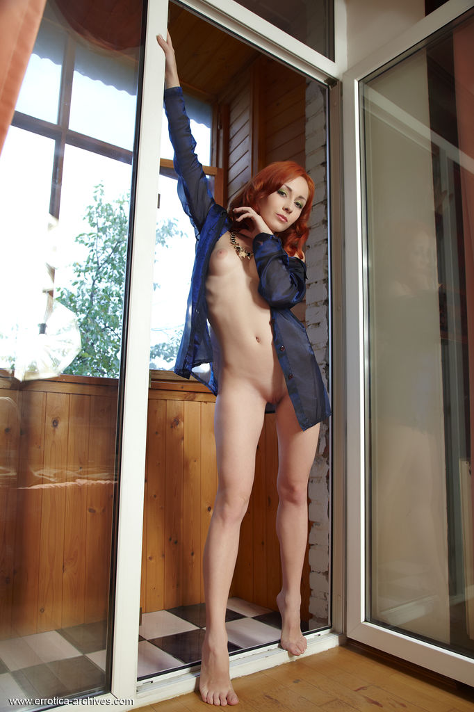 Night, with her seductive gaze, cuppable breasts, round rump and stunning physique poses   erotically by the window.