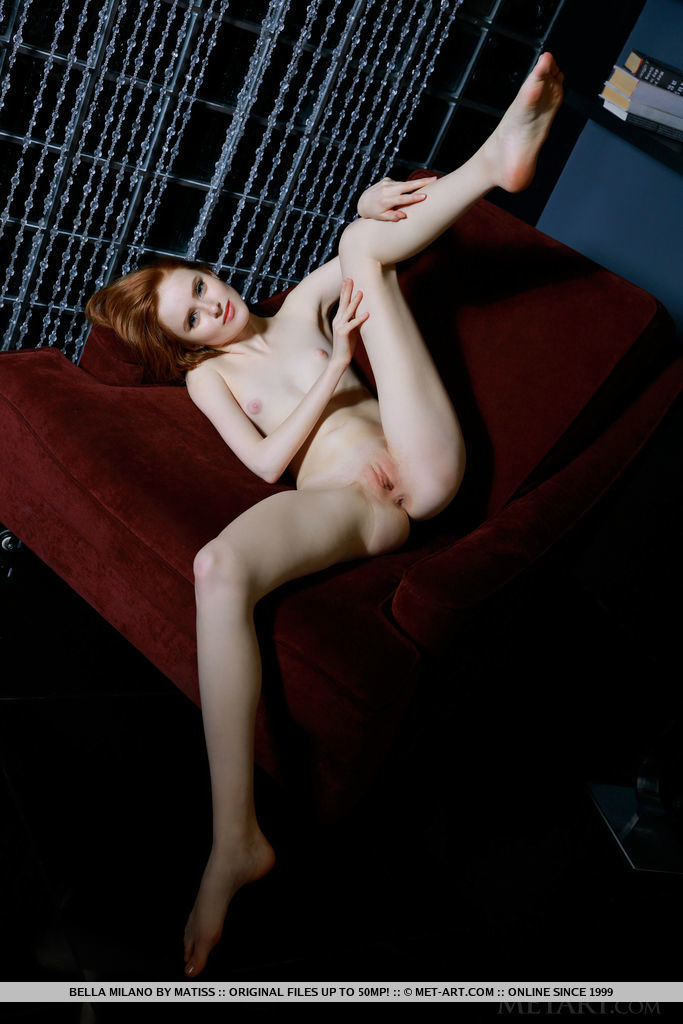 Redhead Bella Milano flaunts her petite body and smooth pussy on the couch.
