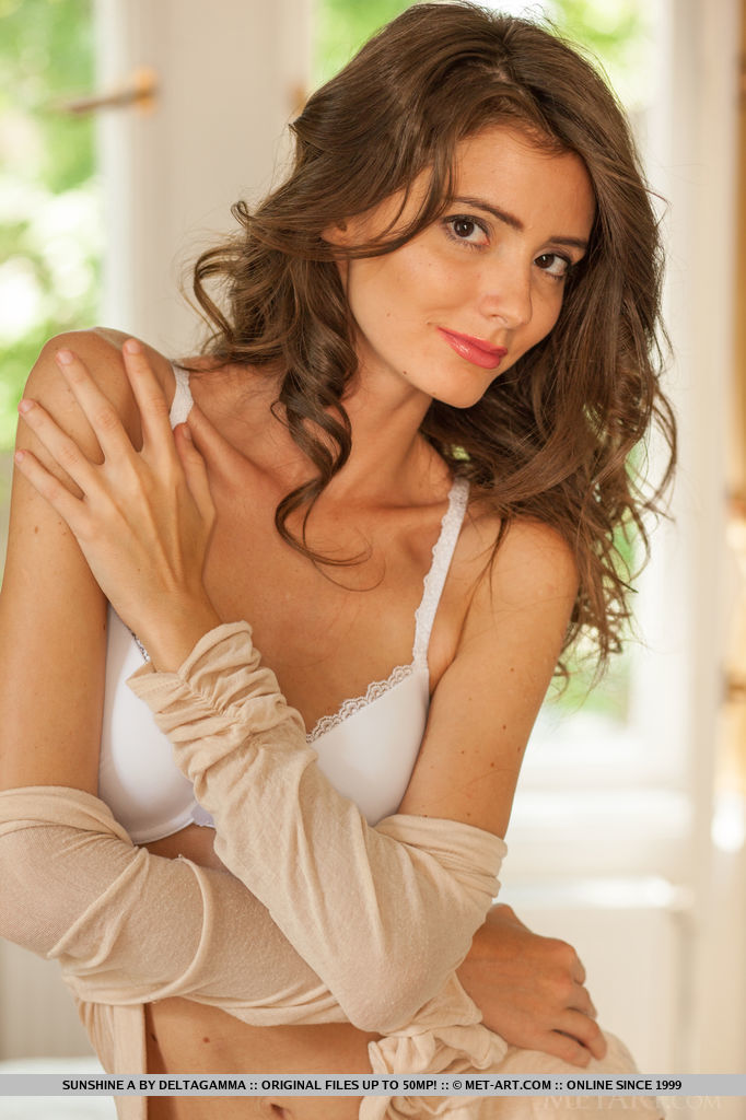 Sunshine A s confident and sensual posing, wearing a dainty white matching lingerie, skintone cardigan, and stiletto shoes that elongate her svelte legs.