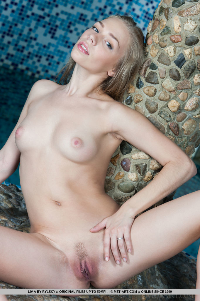 A naked and happy Liv A, her face beaming with a warm and positive smile, greets us with artistic and erotic poses.