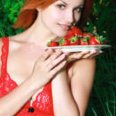 Naughty redhead Violla A posing in her bright red lace lingerie and a plateful of red strawberries, her porcelain skin and wonderful assets stands out in her lush surroundings.