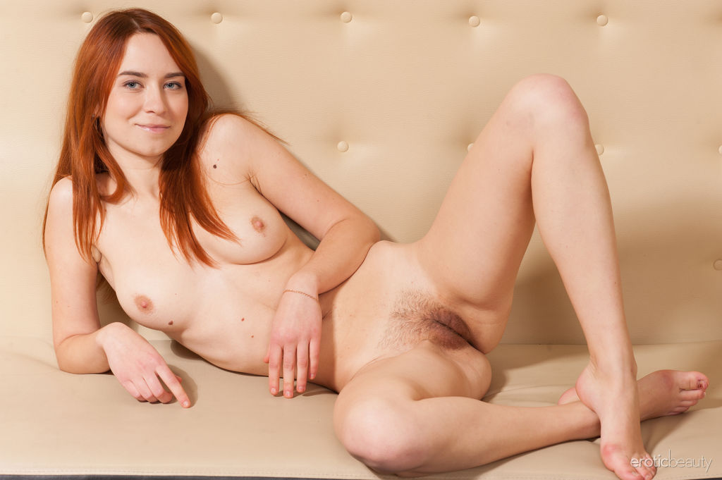Redhead Kelly G bares her trimmed pussy as she poses on the couch.