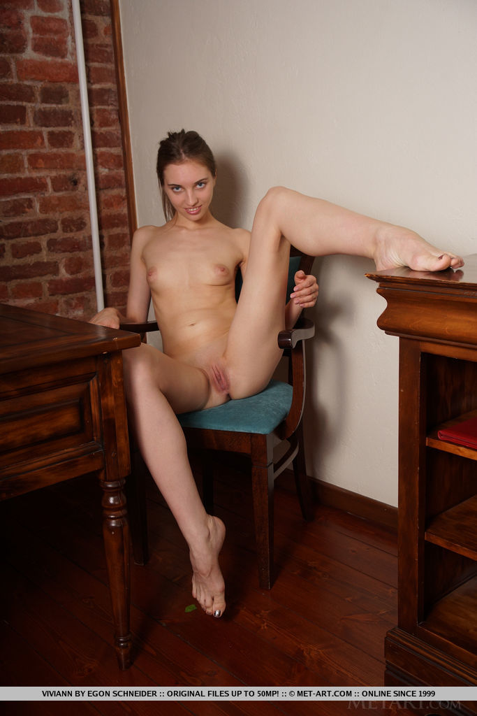Viviann spreads her long legs as she bares her smooth pussy.
