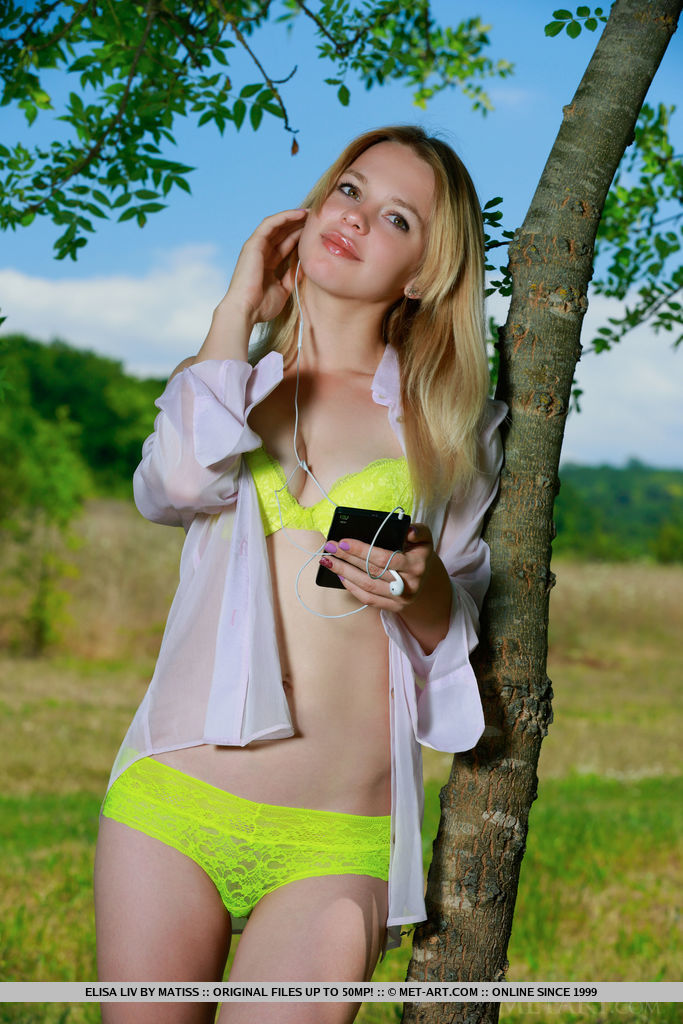 Elisa Liv strips her lime green lingerie baring her nubile body on the grassy field.